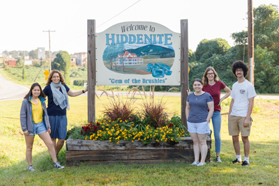 Sharpe Chair and students at Welcome to Hiddenite sign